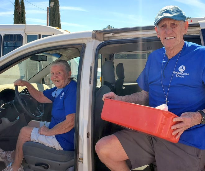 Ruth Ann and Bob Glover, AmeriCorps volunteers, prepare to hit the road with home delivered meals.