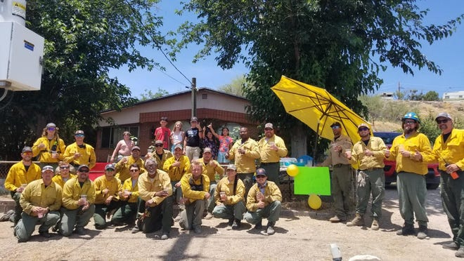Firefighters and kids at lemonade stand at a home in Globe, AZ.