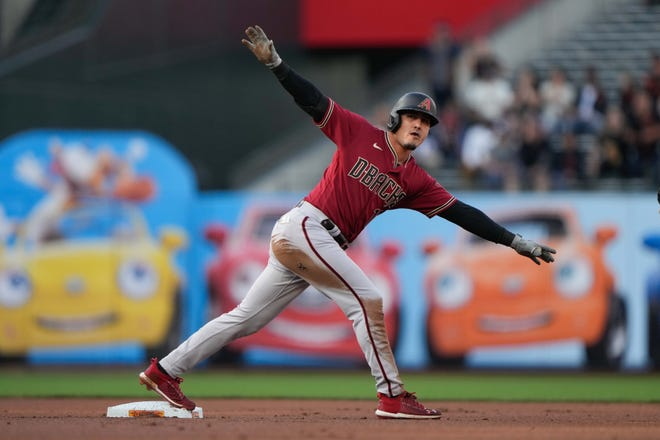 Arizona Diamondbacks third baseman Josh Rojas (10) signals after sliding in safe during the first inning against the San Francisco Giants at Oracle Park.
