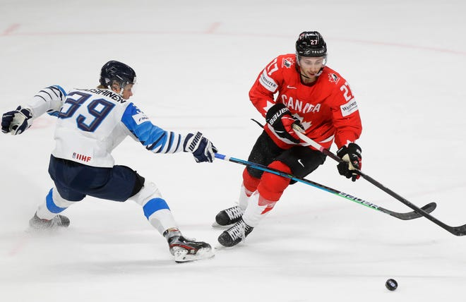 Finland's Kim Nousiainen, left, challenges for the puck with Canada's Michael Bunting during the Ice Hockey World Championship group B match between Canada and Finland at the Arena in Riga, Latvia, Tuesday, June 1, 2021. (AP Photo/Sergei Grits)