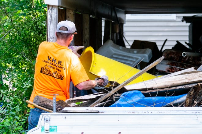 A V.H.R. Lawn Maintenance employee digs through debris next to a shed in a yard being cleaned up by the city Wednesday, June 16, 2021, in Port Huron.
