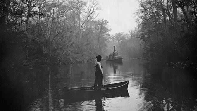 Archival photograph (c. 1880-1897) of a man standing in a canoe, steamboat in background; in Deep Creek, Florida.