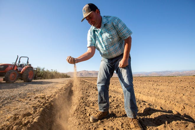 John Werner holds a handful of soil for a portrait in his soon-to-be pistachio grove near Visalia, Calif. on June 10, 2021. He enjoys farming when he is not working as an educator and is planning on planting pistachio trees soon.
