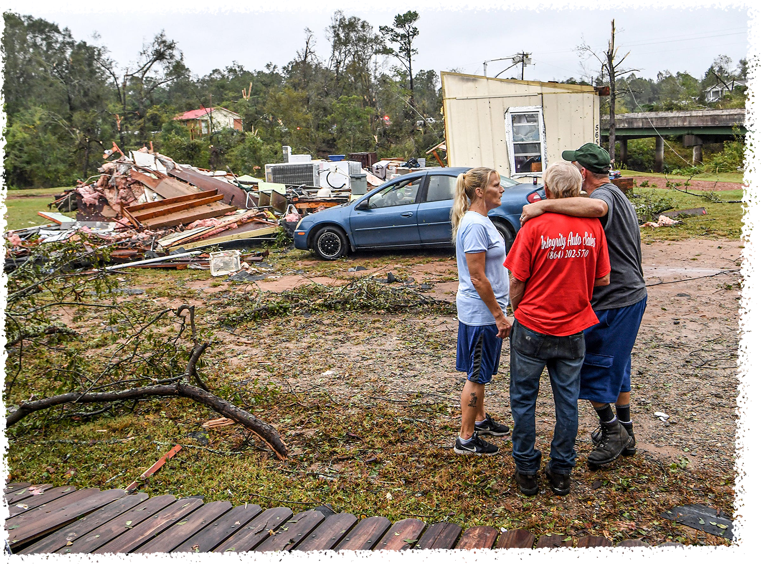 Larry Kelly, right, puts his arm around Jerry Edward Johnston of Central near Kathleen Kelly, left, at the steps of his home on Robinson Bridge Road in Central, S.C., on October 9, 2017.