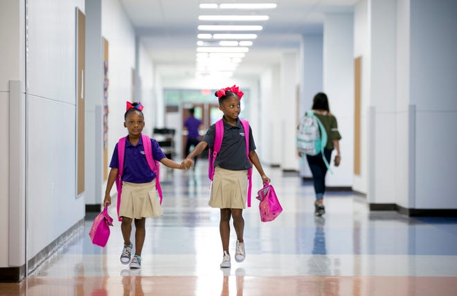 Sisters Coco and Chloe Simpson, shown in 2018, arrive for school at Austin Achieve charter school. The State Board of Education will consider proposals this week for seven more charter schools across the state.