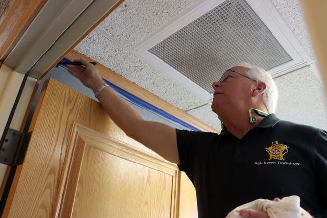Sergeant Byron Towndrow with the Randall County Sheriff's Department paints edges of walls inside The Bridge Children's Advocacy Center as part of the United Way Day of Caring Friday morning.