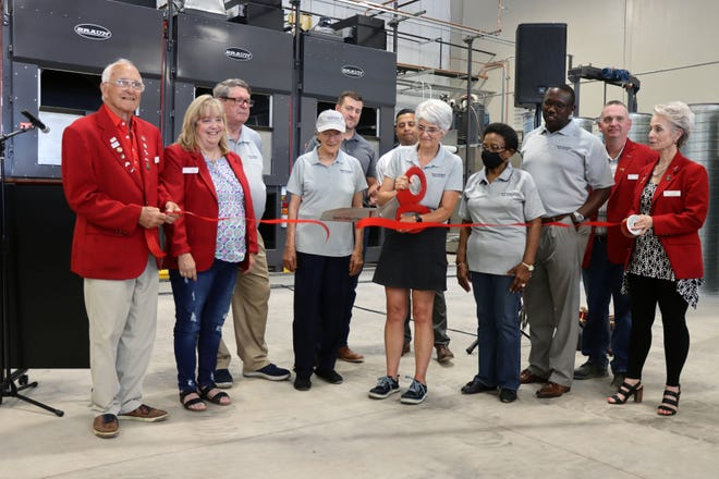Puff Niegos, the president of the North Heights Linen Service, LLC Board of Directors, cuts the ribbon with other members of the board and members of the Amarillo Chamber of Commerce during a ribbon cutting ceremony Thursday afternoon.
