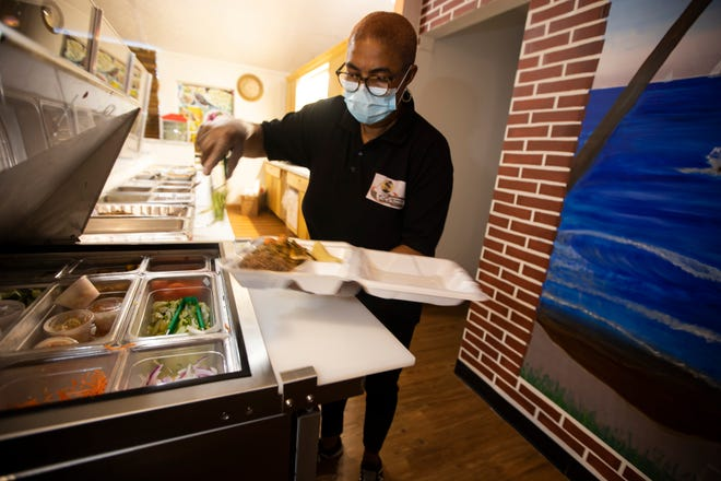 Claucia Dossous, co-owner and chef of T-Co Islands Restaurant, prepares a to-go container at the restaurant in Columbus, Ohio June 18. T-Co Islands specializes in Haitian cuisine and is located on Cleveland Ave and Morse Rd.