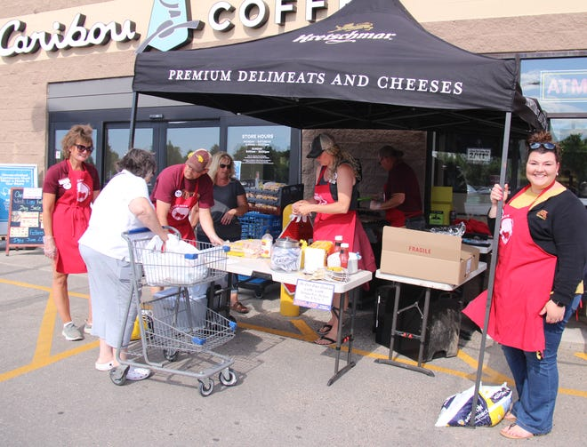 UMN Crookston staff, along with Ox Cart Days Planning Committee leader Theresa Tahran, in gray shirt, help a customer at the Hugo's cookout Thursday. Smiling for the camera on the right is Brooke Novak.