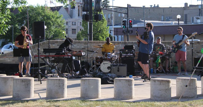 Anthony Diaz, right center on guitar in blue shirt, and his band perform outside the Crookston Library Thursday evening.
