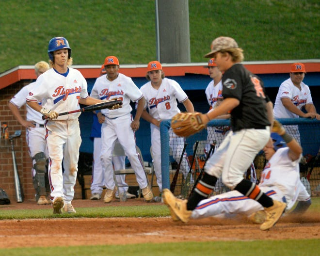 Randleman's Owen Strickland (with bat) looks on as teammate Andrew Cox slides home on a passed ball in the bottom of the fifth inning against Southwest Onslow in the second round of the 2-A state playoffs. Cox's run ended the game in the Tigers' 10-0 win. [Mike Duprez/Courier-Tribune]