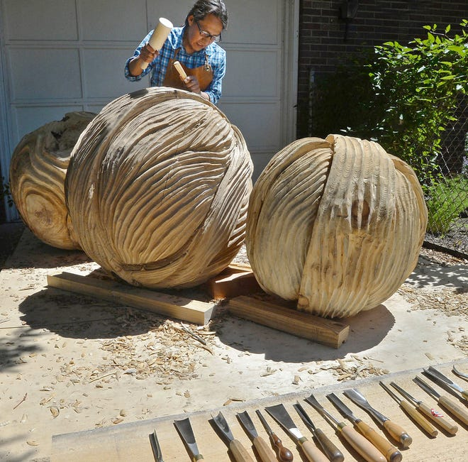 """Artist Fredy Huaman Mallqui works on his sculpture """"Together"""" on Wednesday, in the driveway of his Erie home. The piece is one of 13 selected for the new Downtown Erie Sculpture Walk, with works to be installed through early July."""