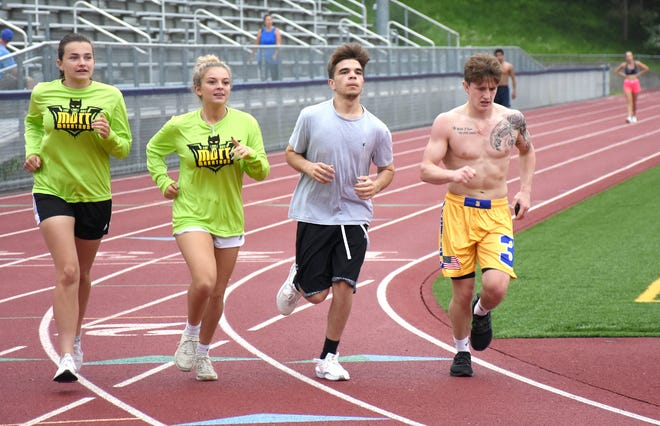Mason Bush (right), the top finisher Monday at the 15th Mott Marathon at Central Valley Academy, is joined by members of his support team (from left) Keeley Tutty, Gianna Frank and Kaden Olds during one of the final laps of the 105-lap run around the Diss Memorial Athletic Complex track.