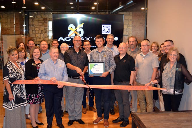 Members of AgTrax, a Hutchinson agribusiness software company, are joined by the Hutchinson Chamber of Commerce for a ribbon cutting at its new location at 10 S. Main, Suite A, on Thursday.