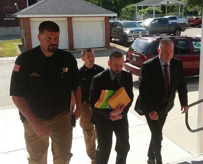 Gary Berchtold is escorted by police officers into the Marshall County courthouse for the second day of his bench trial on murder and other charges stemming from the death of Tiffini Murphy. He was found guilty by Circuit Judge James Mack of shooting her to death, burning her body, and dumping the remains.