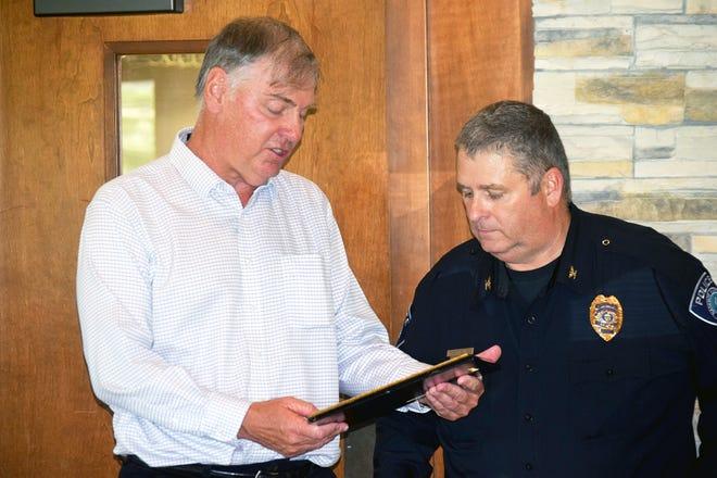 Basehor Mayor David Breuer presents a plaque to retiring Police Chief Bob Pierce on Thursday during a retirement reception.
