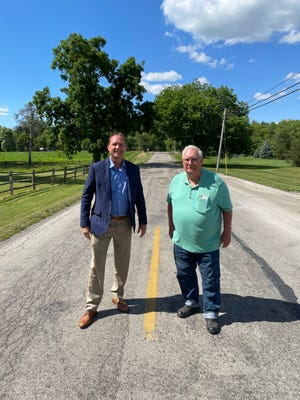 Bedford Township Supervisor Paul Pirrone (left) and Whiteford Township Supervisor Walter Ruhl pose for a photo on Adler Rd. last week, just before repair and resurfacing work was scheduled to begin.