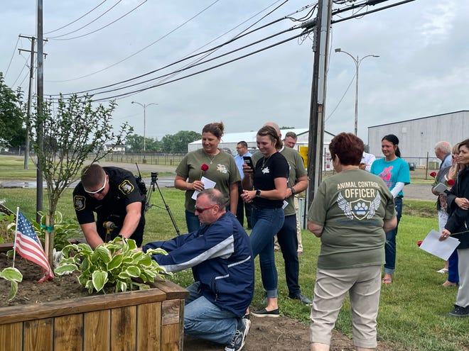 A tree was planted in honor of former animal control officer Darrian Young. Her father, Aaron Young helped to install her memorial plaque while surrounded by Darrian's mother, Tammi Kamprath, sister Darby Young and grandmother, Pat Kirby.
