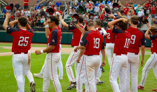 New Boston Huron's baseball players tip their caps to Orchard Lake St. Mary's after the Eaglets won 5-1 in the Division 2 state semifinals Friday at Michigan State University.