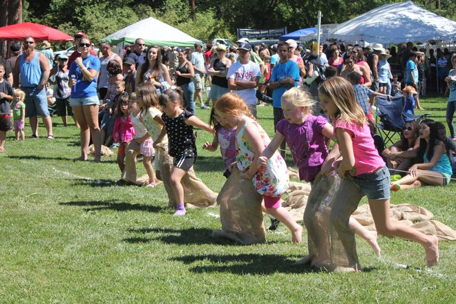 Children have fun in a three-legged race at a past Blackberry Music Festival at Mount Shasta City Park.