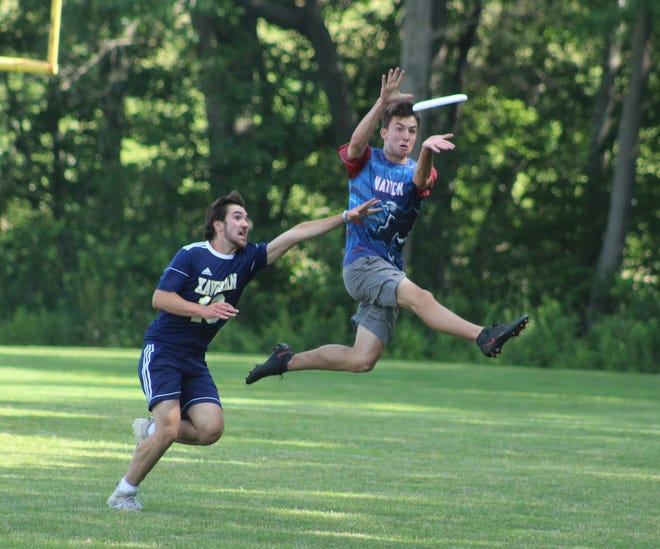 Myshkin Munson (right) leaps to make the catch for Natick in the Ultimate Frisbee state finals against Xaverian on Thursday, June 17, 2021 at Natick High School.