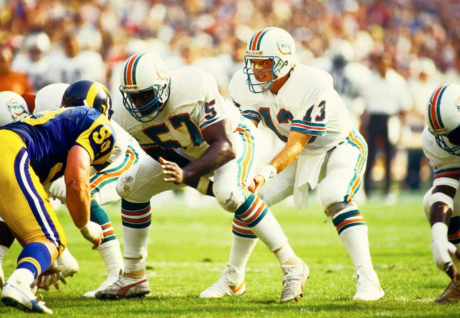 Dwight Stephenson snaps the football to Dan Marino during a game against the Rams in 1986. Both are in the Pro Football Hall of Fame.