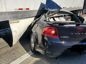 A car is pinned beneath a big rig on northbound Interstate 5 near Benjamin Holt Drive on Friday morning. Trucker John Hughes of Stockton was first on scene and pulled the driver and female passenger from the car, cutting himself as he lifted the windshield off of her.