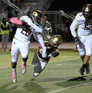Edison runner Nakian Jackson gets dragged down by Stagg linebacker Joel Aparicio during a game at Stagg.