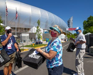 Volunteer Tom Klotter, left, hands out free samples to Lois and Arnold Holloway from Dundee outside Hayward Field as the Olympic Trials begin on Friday.