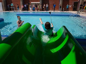 Frank Cerda, 11, goes down the water slide with a GoPro camera in hand during an opening ceremony Thursday for the remodeled Echo Hollow Pool in Eugene.