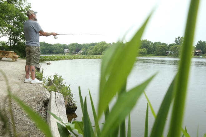 Tyler Moncrief, a Canton Township resident, casts his line Friday while fishing at Sippo Lake in Perry Township. He fishes several times a week.