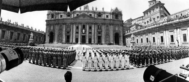 """Wide angle view of St. Peter's Square on June 21, 1963 shortly after noon as honor units of the Italian armed forces are lined up while the newly elected Pope Paul VI, formerly Giovanni Battista Cardinal Montini, archbishop of Milan, gives his first blessing """"Urbi et Orbi"""" (to Rome and to the World) from the central balcony of St. Peter's, background. What look as mouths of pieces of artillery in foreground are simply the mouths of some of the many long lens cameras pointed at the Basilica."""