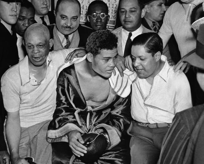 Here are Joe Louis, center, sits with his crew after he knocked out champ Jim Braddock in eight rounds for the world heavyweight championship. At left are trainer Jack Blackburn and co-managers Julian Black, right, and  John Roxborough (with mustache) in Chicago on June 22, 1937.