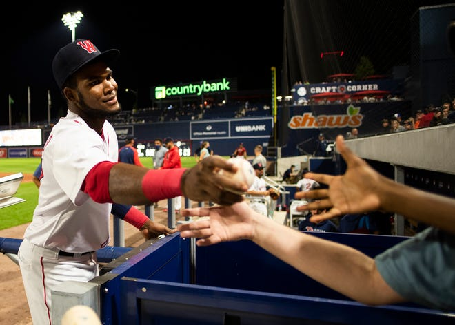 Franchy Cordero hands off signed baseballs to young fans after a recent game.