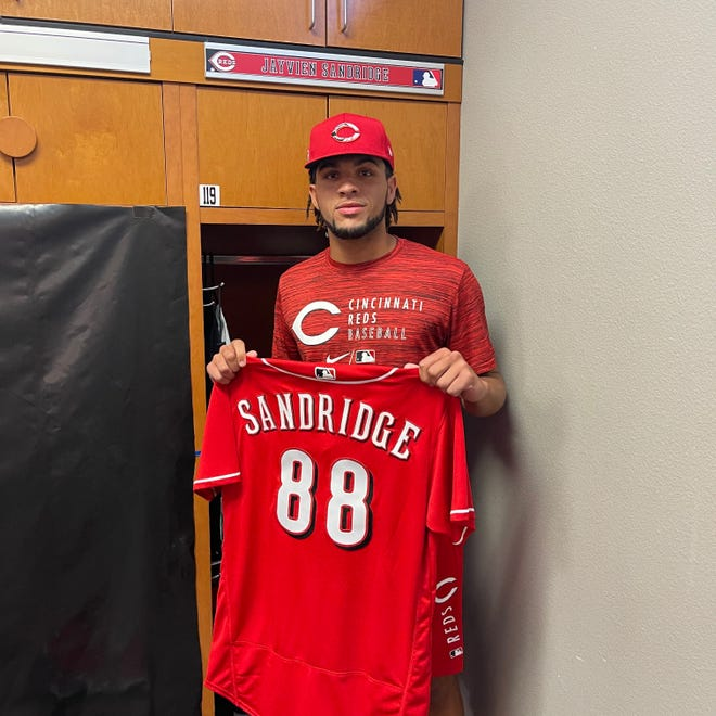 Hagerstown's Jayvien Sandridge shows off his new wardrobe, including his jersey, after signing a free agent contract with the Cincinnati Reds. Sandridge was drafted by the Orioles and released.