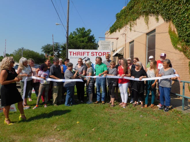 Virginia Sevier, organizer of the Love Your Neighbor thrift store, cuts the ribbon at the grand opening of the store on Friday.