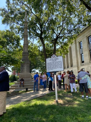 Supports who attended the marker honoring Black soldiers from Madison County who fought in the Civil War mingle around the marker and the Confederate soldier statue after the event.