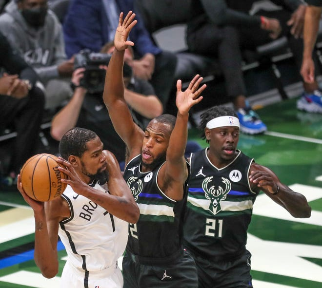 Nets forward Kevin Durant can't find any room to operate against the Bucks' Khris Middleton and Jrue Holiday.