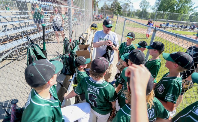 Mike Schultz shows his players the new baseball jerseys he got for them to wear during a tournament Friday at Wirth Park. This is Schultz's first time back coaching a tournament since spending three months in a medically induced coma due to COVID-19.