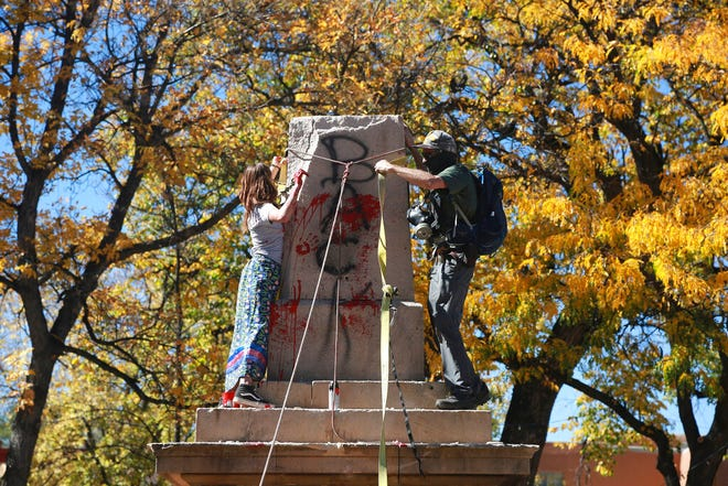 In this Saturday, Oct. 12, 2020, file photo, demonstrators secure a rope around the centerpiece of a solid stone obelisk before tearing it down in Santa Fe, N.M. The Hispanic cultural association Union Protectiva de Santa Fe sued the city's mayor Wednesday, June 16, 2021, over the destruction of the obelisk by activists last year and plans to move the memorial permanently. The lawsuit argues that the obelisk, which honors Hispanic soldiers that fought and died for the Union in battles with Confederate soldiers and Indigenous tribes, is a protected historical site.