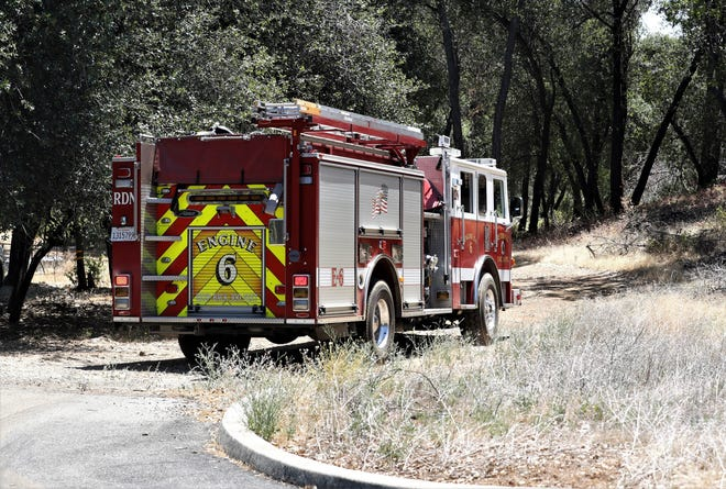 Firefighters aboard Engine 6 head to a vegetation fire at the east end of Mistletoe Lane after loading up with water from a hydrant at the nearby Redding Christian Fellowship Church on Friday, June 18, 2021.