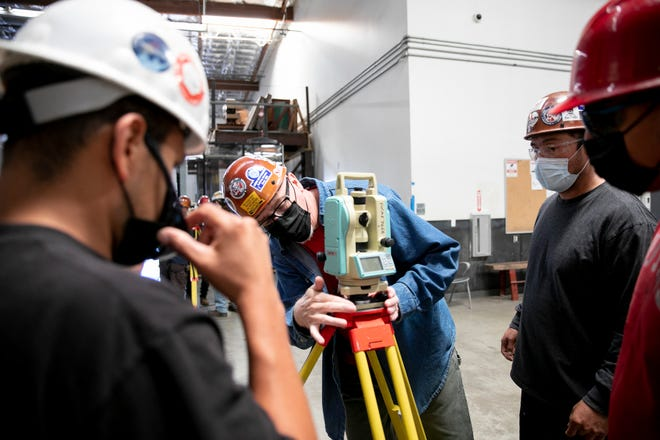 Apprenticeship instructor Mike Miller, center, demonstrates how to set up a theodolite, a hyper-sensitive angle measuring device, for apprentices Daniel Rivas, left, Ivan Aguilar, right, and Quetzalcoatl Orta, far right, at Iron Workers union in Benicia on June 10, 2021.