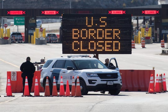 U.S. Customs officers stand beside a sign saying that the U.S. border is closed at the U.S./Canada border in Lansdowne, Ontario, on March 22, 2020.