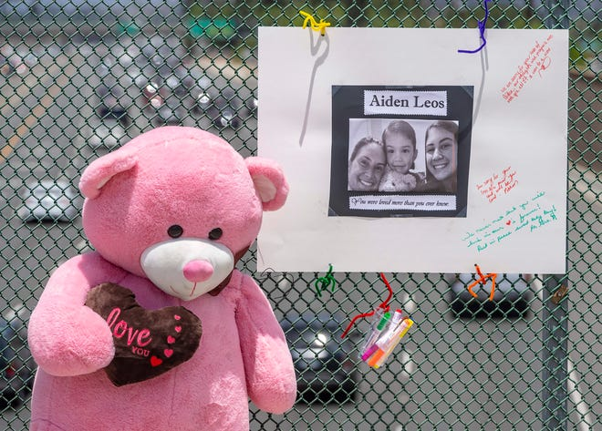 A large stuffed toy bear and a poster board with a photo and notes are part of a memorial for Aiden Leos, the 6-year-old boy who was shot and killed during a suspected road-rage attack in Southern California in late May.