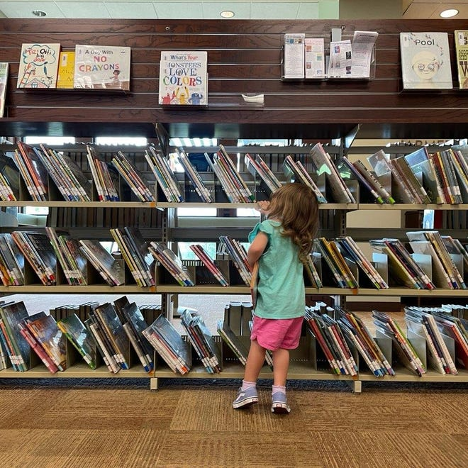 Three-year-old Daisy Roberts browses through the selection of books at the newly reopened Laura's Library.