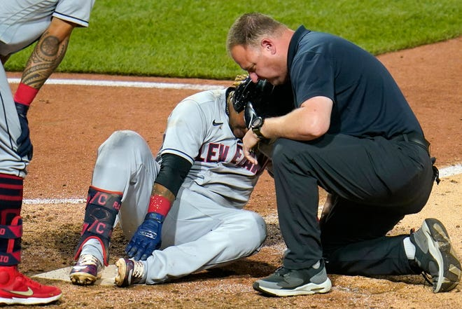 Cleveland's Jose Ramirez holds his ankle after being hit by a pitch from Pittsburgh reliever Kyle Crick during the eighth inning in Pittsburgh, Friday, June 18, 2021. Ramirez left the game. (AP Photo/Gene J. Puskar)