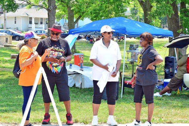 Longtime friends Vicky Brown Moore, Elias King, Vanessa Brown-Haywood and Teresa Garr chat Saturday at Douglass Park during the Juneteenth block party.