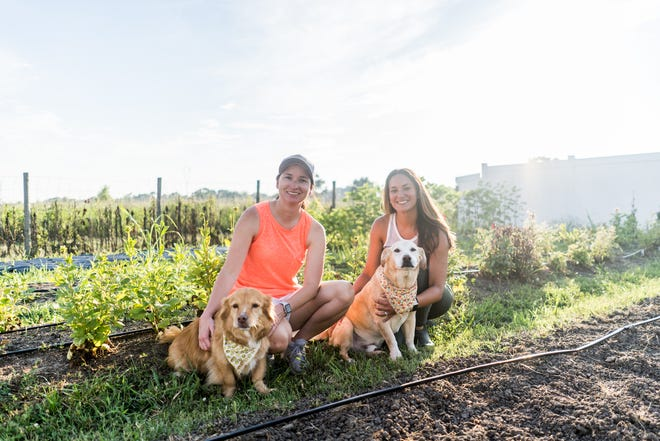 TerriLynn and Reesa Gravois-Arabie pose with their dogs at their small flower farm in Lockport.