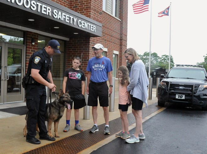 Wooster police patrolman Phil Coe shows police dog Lex to Caleb Mitchell, Doug Patton, Annie Mitchell and Beth Patton outside the Wooster Safety Center building Saturday during the city's Walk, Run & Roll Scavenger Hunt.
