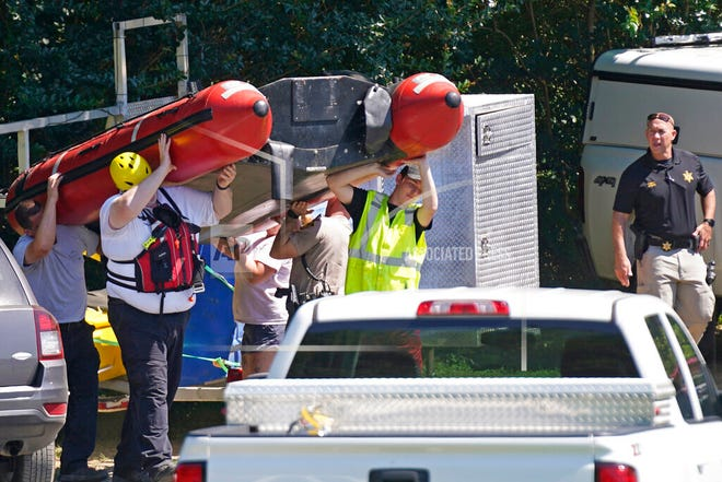Rescue personnel stage along the Dan River in Eden, N.C., Friday, June 18, 2021. The search for two missing tubers continues after three others were found dead and four more were pulled from the water after the group went over an 8-foot dam Wednesday. (AP Photo/Gerry Broome)
